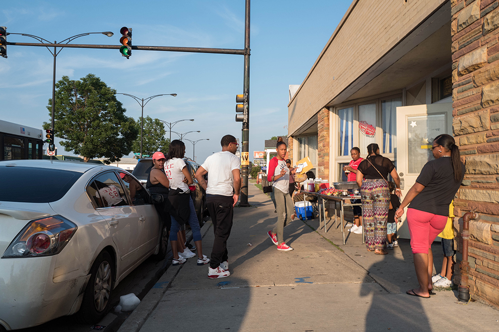 A group gathers in front of a store on 79th Street in Ashburn. (Courtesy Jason Schumer/City Bureau)