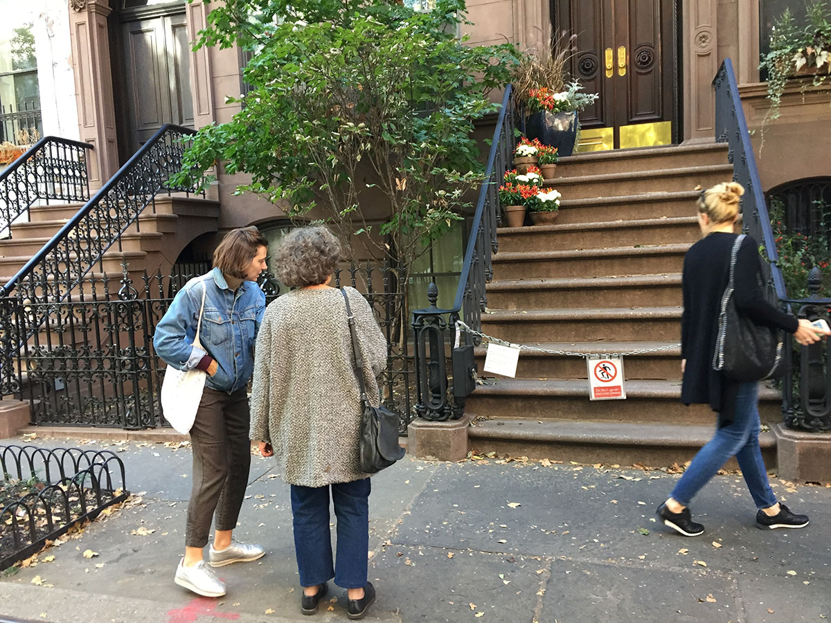"People view the New York brownstone stoop that was featured as Carrie Bradshaw's rent-controlled apartment in ""Sex and the City."" The building is located in Greenwich Village, but portrayed as the Upper East Side on the series. (AP Photo/Beth J. Harpaz)"