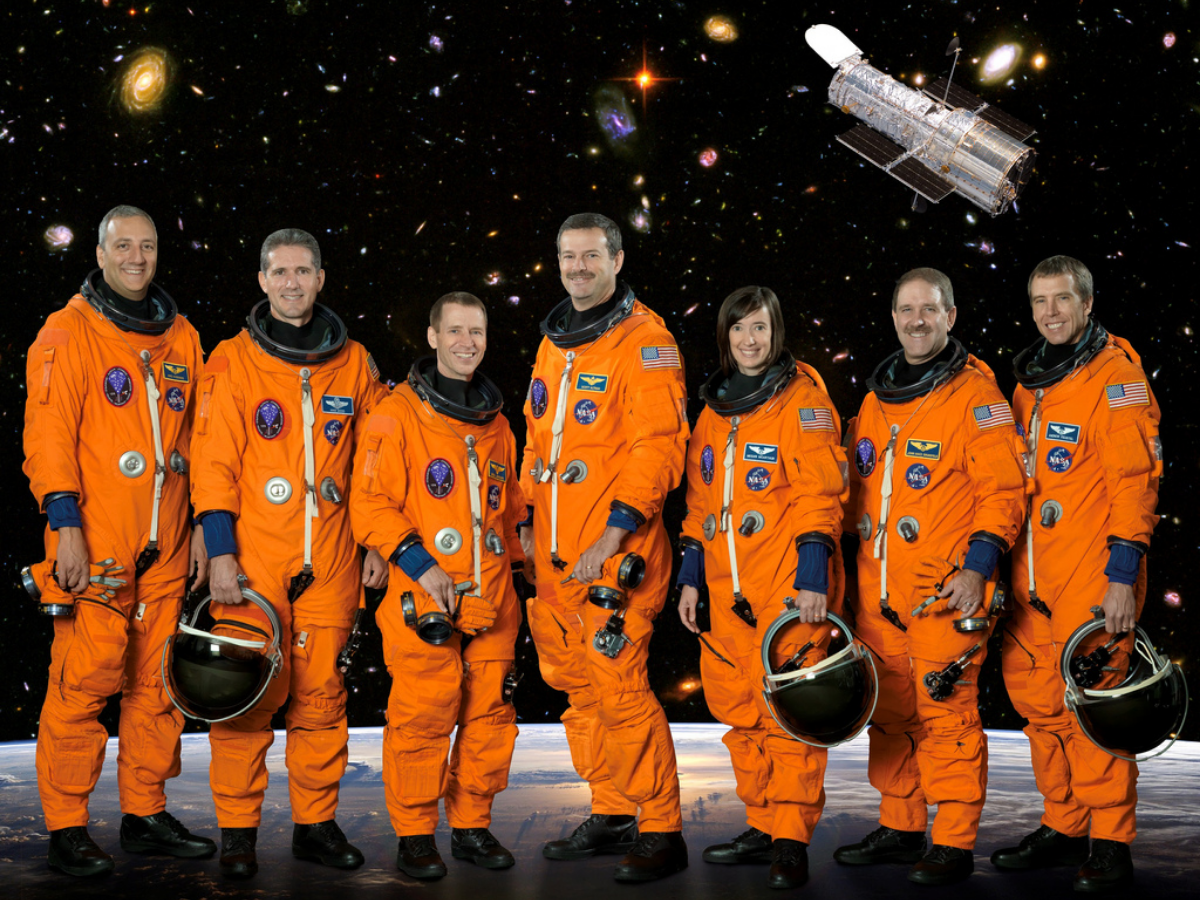 These seven astronauts take a break from training to pose for the STS-125 crew portrait. From the left are astronauts Michael J. Massimino, Michael T. Good, both mission specialists; Gregory C. Johnson, pilot; Scott D. Altman, commander; K. Megan McArthur, John M. Grunsfeld and Andrew J. Feustel, all mission specialists. (Photo courtesy of NASA)