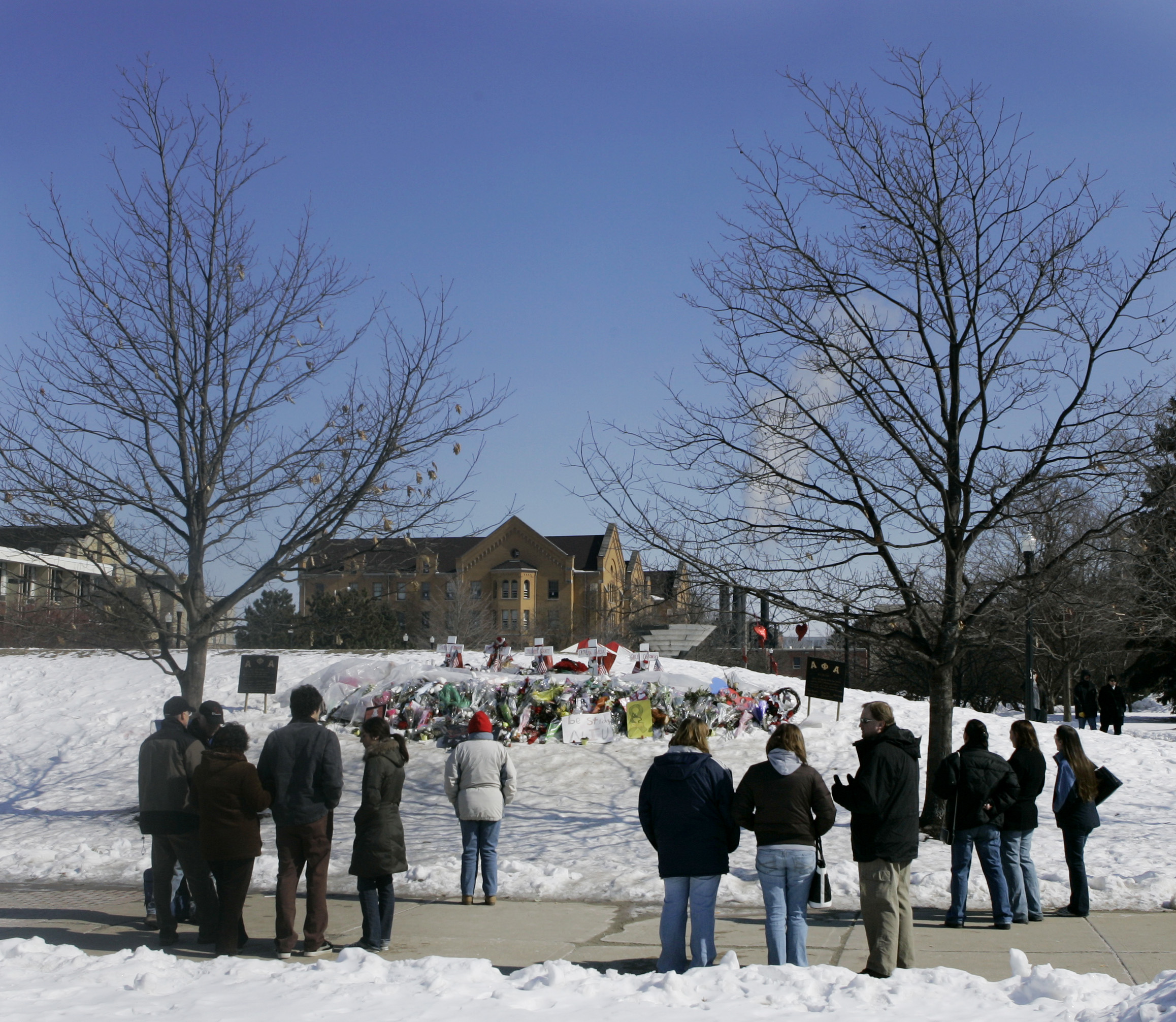 Mourners gather near a memorial to the five students who were killed during the Valentines Day shooting at Northern Illinois University in De Kalb, Ill., Saturday, Feb. 23, 2008. (AP Photo/Charles Rex Arbogast)