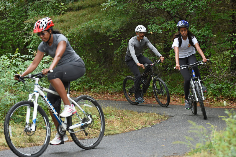 President Barack Obama rides bikes with his wife, Michelle, and daughter, Malia, on Martha's Vineyard in August 2015. (Susan Walsh/AP)