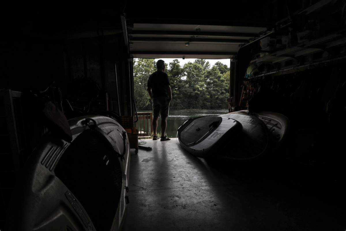 Tom Monahan, owner of Kickapoo Adventures in Oakwood, Illinois, stands in his business looking out at the Vermilion River. (Sebastián Hidalgo/WBEZ)