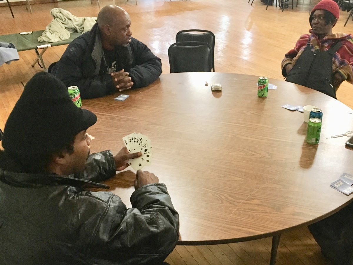 Michael Brothers plays plays cards with other homeless friends he met at the shelter. (Michael Puente/WBEZ)