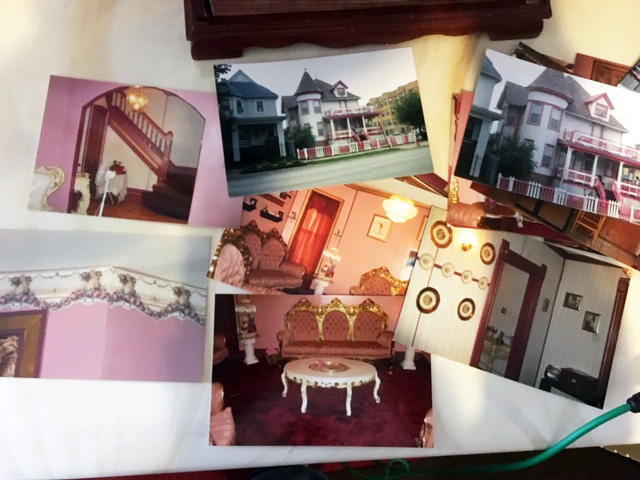 On a table in the so-called Barbie Dreamhouse, photos are spread out on a table showing the house's interior, including its hot pink carpet and pink and rose-designed walls. (Lakeidra Chavis/WBEZ)