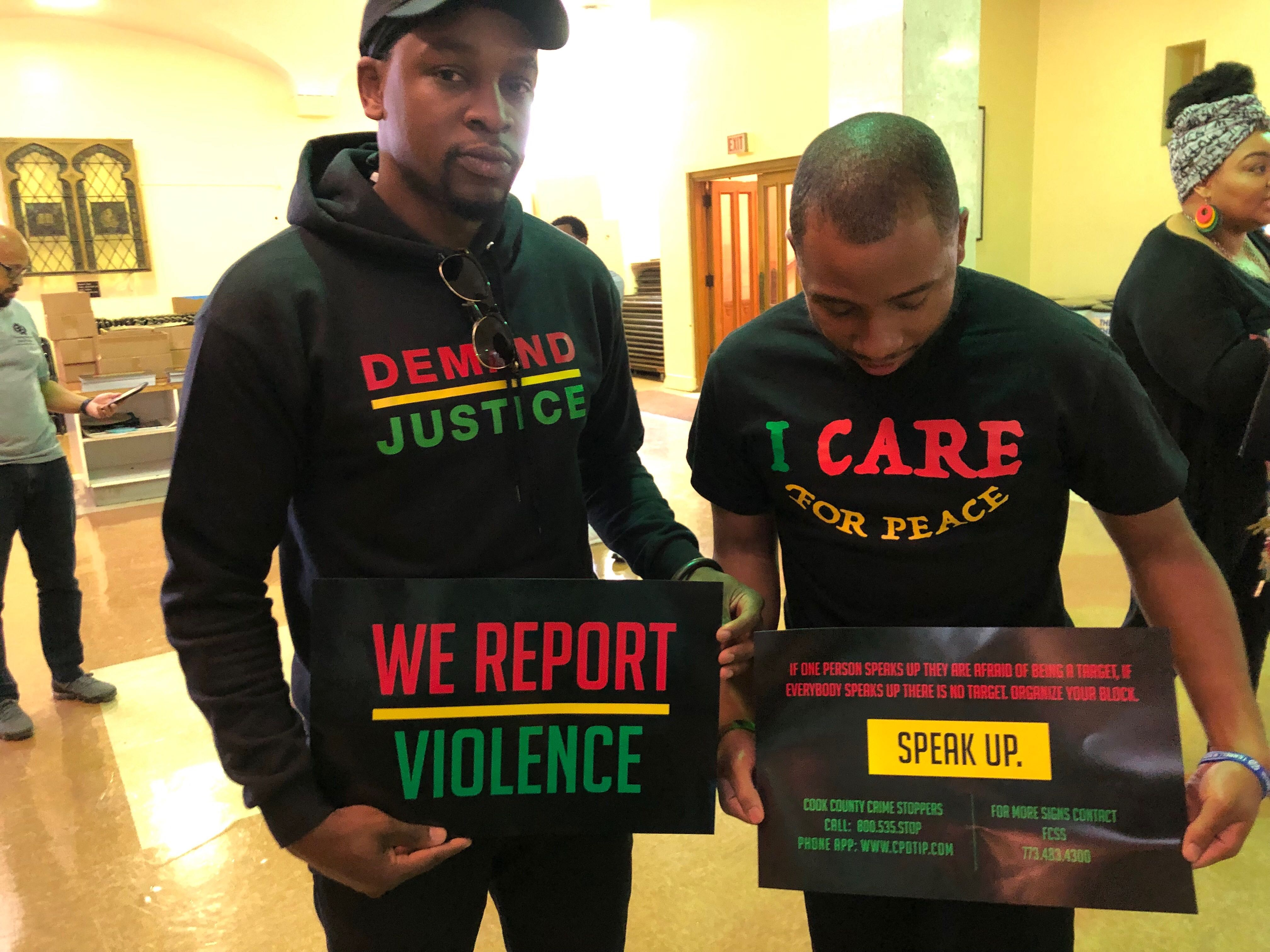Maxwell Emcays (left) designed the signs that organizers distributed Wednesday at St. Sabina. Father Michael Pfleger asked attendees to display the signs in their windows or on their doors.