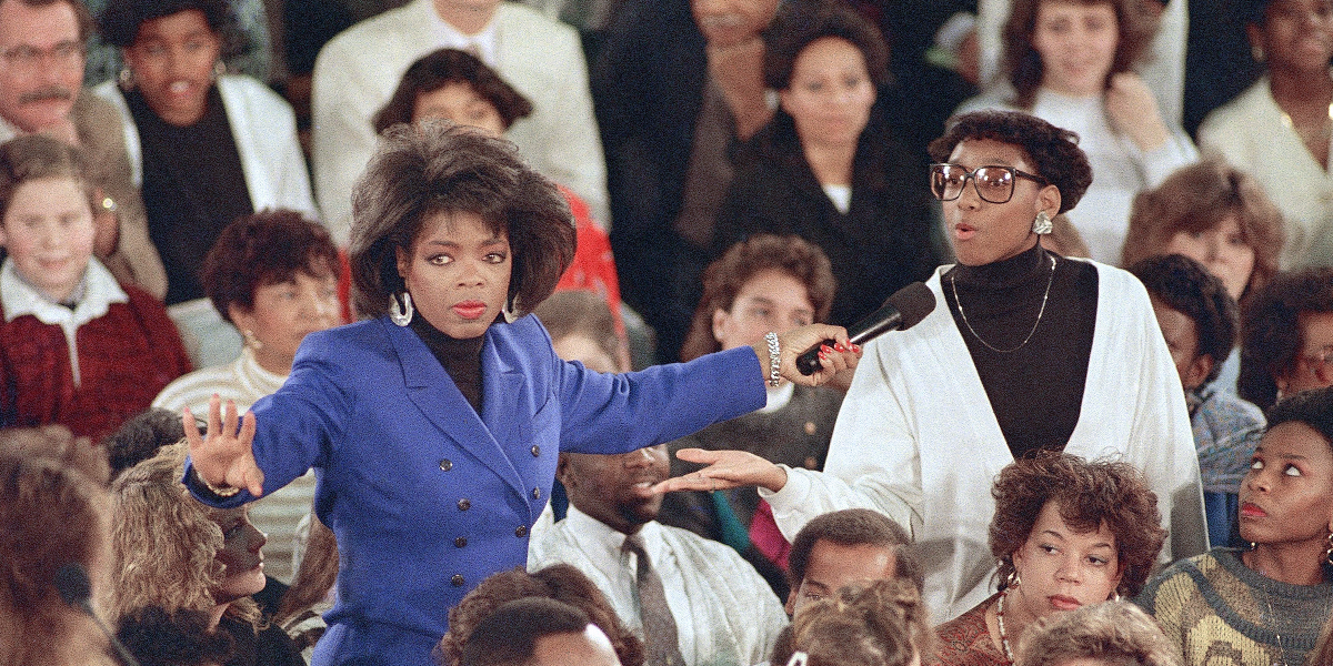 Oprah Winfrey gestures to the crowd at the Southwestern High School in Baltimore on Nov. 29, 1988. (Jason Lee/AP)