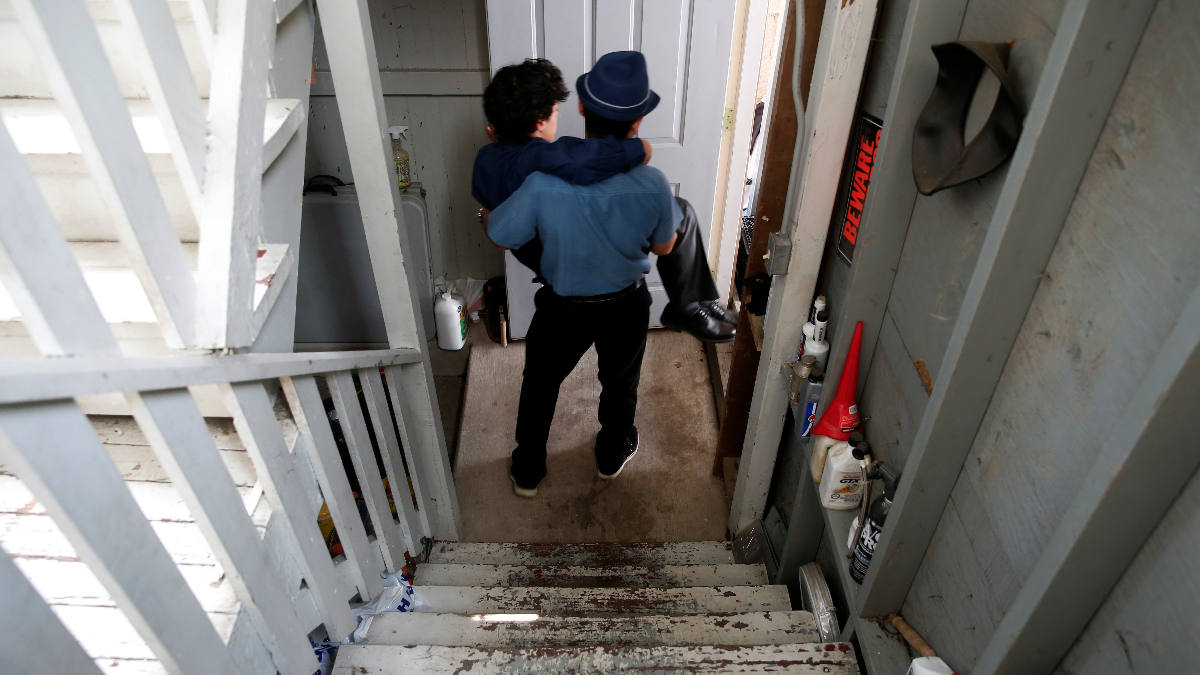 Joshua Annicks carries his brother, Jonathan, to the family car for Jonathan's high school graduation ceremony in Chicago on June 13, 2016. (AP Photo/Charles Rex Arbogast)