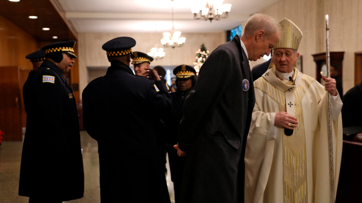 Illinois Gov. Bruce Rauner, second from right, and Cardinal Blase Cupich, right, speak before the funeral for Chicago Police Officer Conrad Gary, Friday, Dec. 21, 2018 at St. Rita of Cascia Shrine Chapel in Chicago. (Abel Uribe/Chicago Tribune via AP, Pool)
