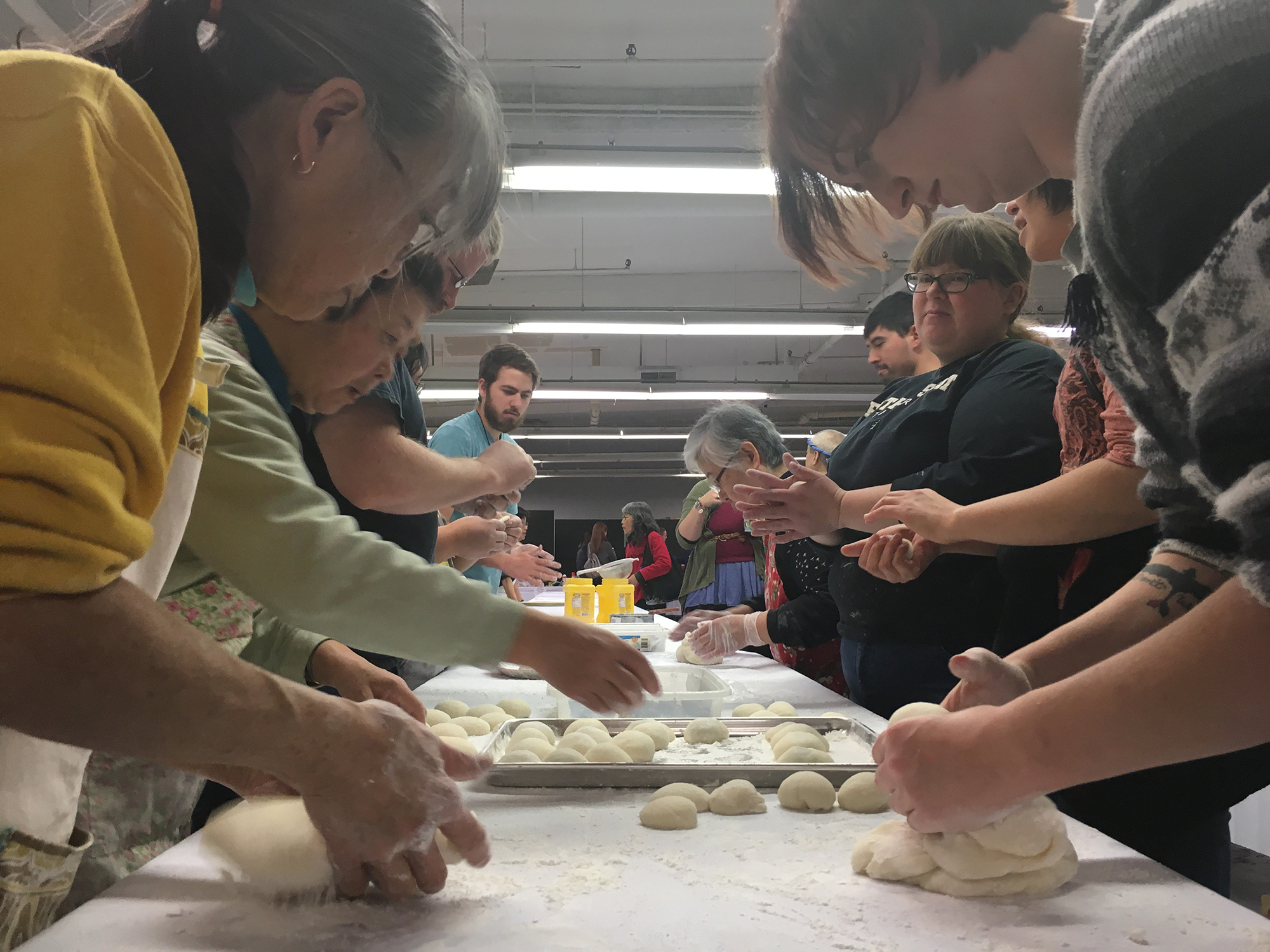 People line a long table to pinch the dough into mochi patties. (Courtesy of the Japanese American Service Committee)
