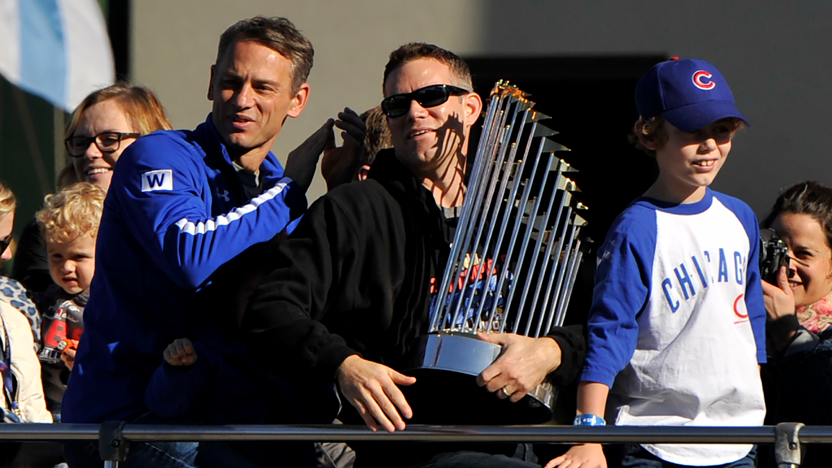 Chicago Cubs president of baseball operations Theo Epstein holds the Commissioner's Trophy while son, Jack, right, and Cubs vice president of baseball operations and general manager Jed Hoyer, left, look on during a parade honoring the World Series champions on Nov. 4, 2016. (AP Photo/Paul Beaty)