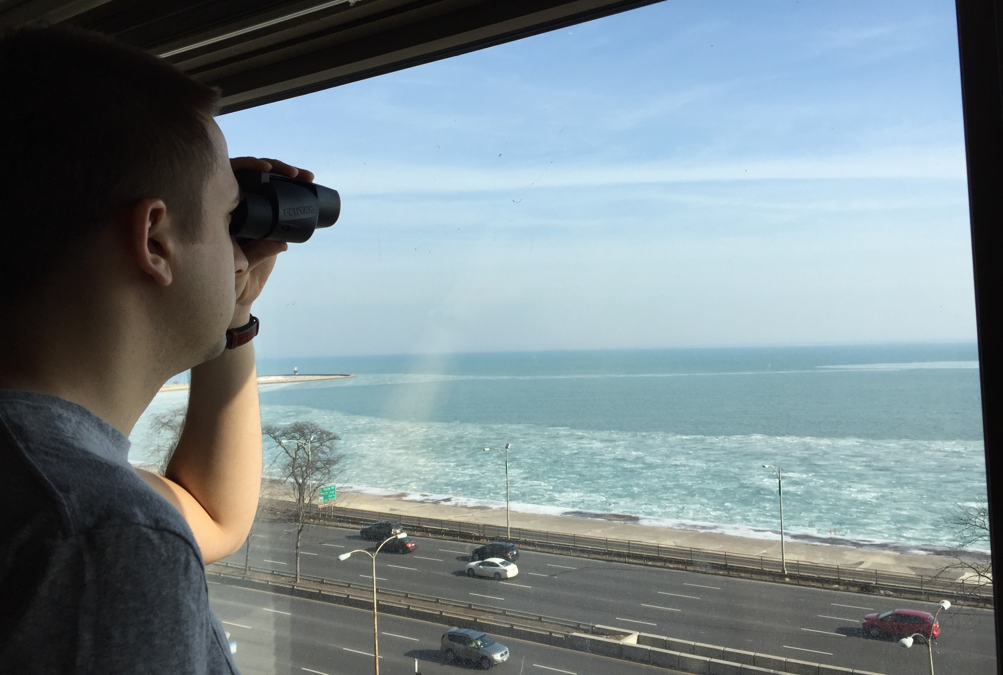 Mike Couzens peers out at ships on Lake Michigan's horizon from his Gold Coast apartment. (Courtesy Mike Couzens)