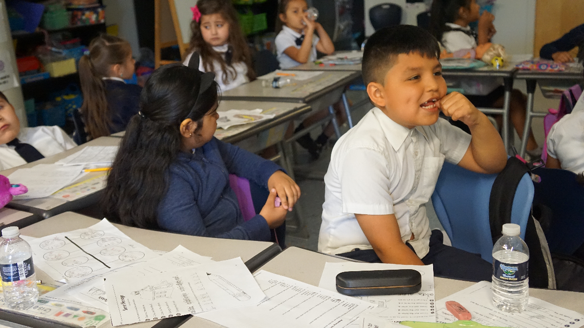 Zizumbo elementary first-grade students share their homework, switching from English to Spanish. (Adriana Cardona Maguigad/WBEZ)