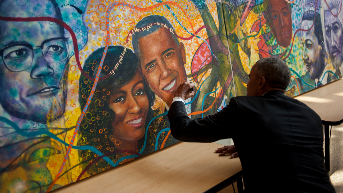 Former President Barack Obama signs a mural in the lobby of Solorio Academy High School that includes him and Michelle Obama. (Bill Healy/WBEZ)