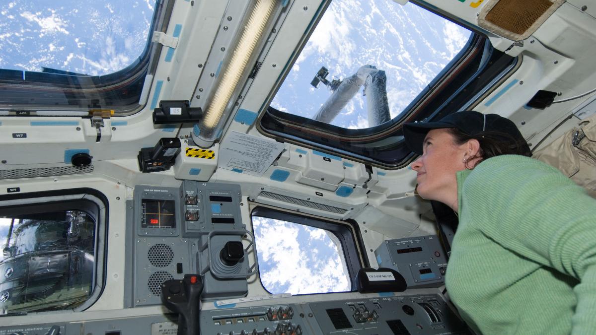 Astronaut Megan McArthur looks through an overhead window on the aft flight deck of Space Shuttle Atlantis during flight day six activities on May 16, 2009. (Photo courtesy of NASA)