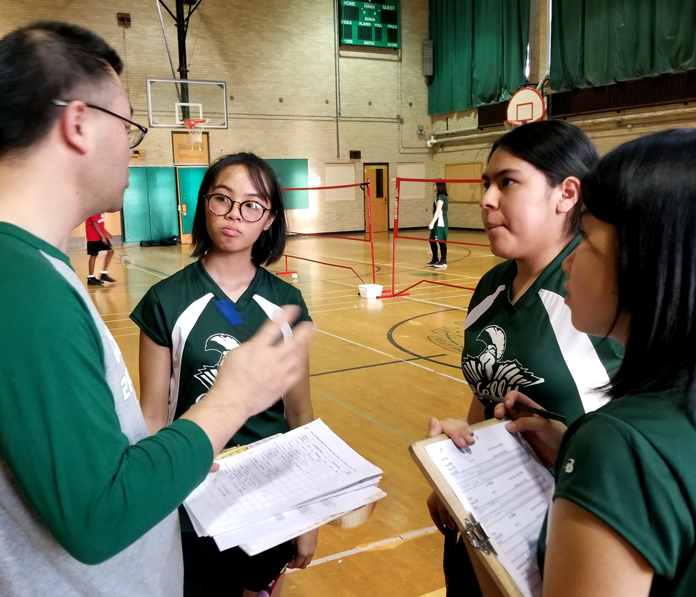 Kelly High School badminton coach Dongyu Bao talks to his players before a game. Dao says offering a sport played in China has helped his Chinese immigrant students feel at home at Kelly. (Linda Lutton/WBEZ)