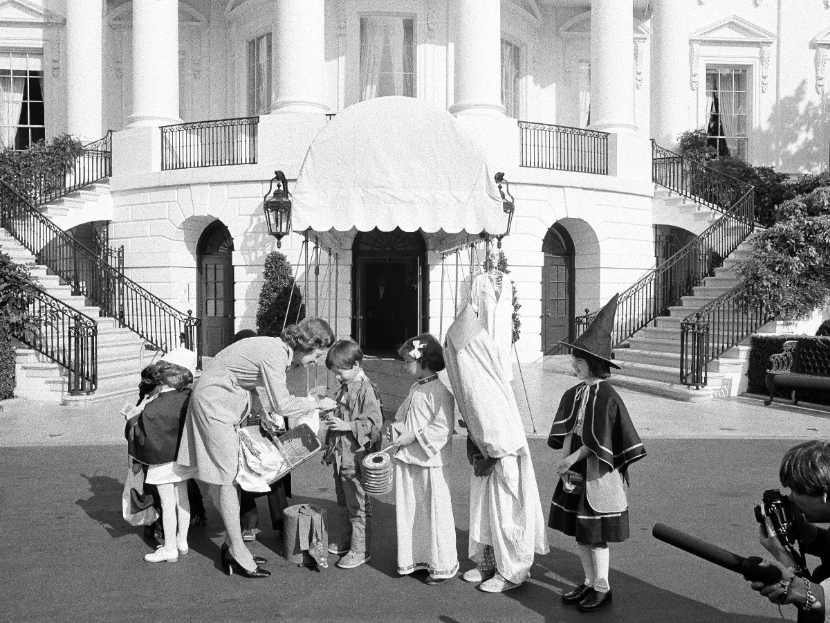 First lady Betty Ford greets costumed school children on Halloween 1974. Mrs. Ford gave each of the children a bag of trick-or-treat candy, an apple, and reached into her pocket to put a quarter coin into the UNICEF collection boxes they carried. (AP Photo/Henry Griffin)