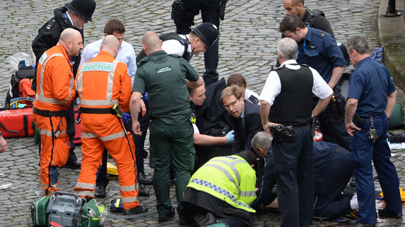 Conservative MP Tobias Ellwood helps emergency services attend to a police officer outside the Palace of Westminster, London, after a policeman was stabbed and his apparent attacker shot by officers in a major security incident at the Houses of Parliament. (Stefan Rousseau/PA Images via Getty Images)