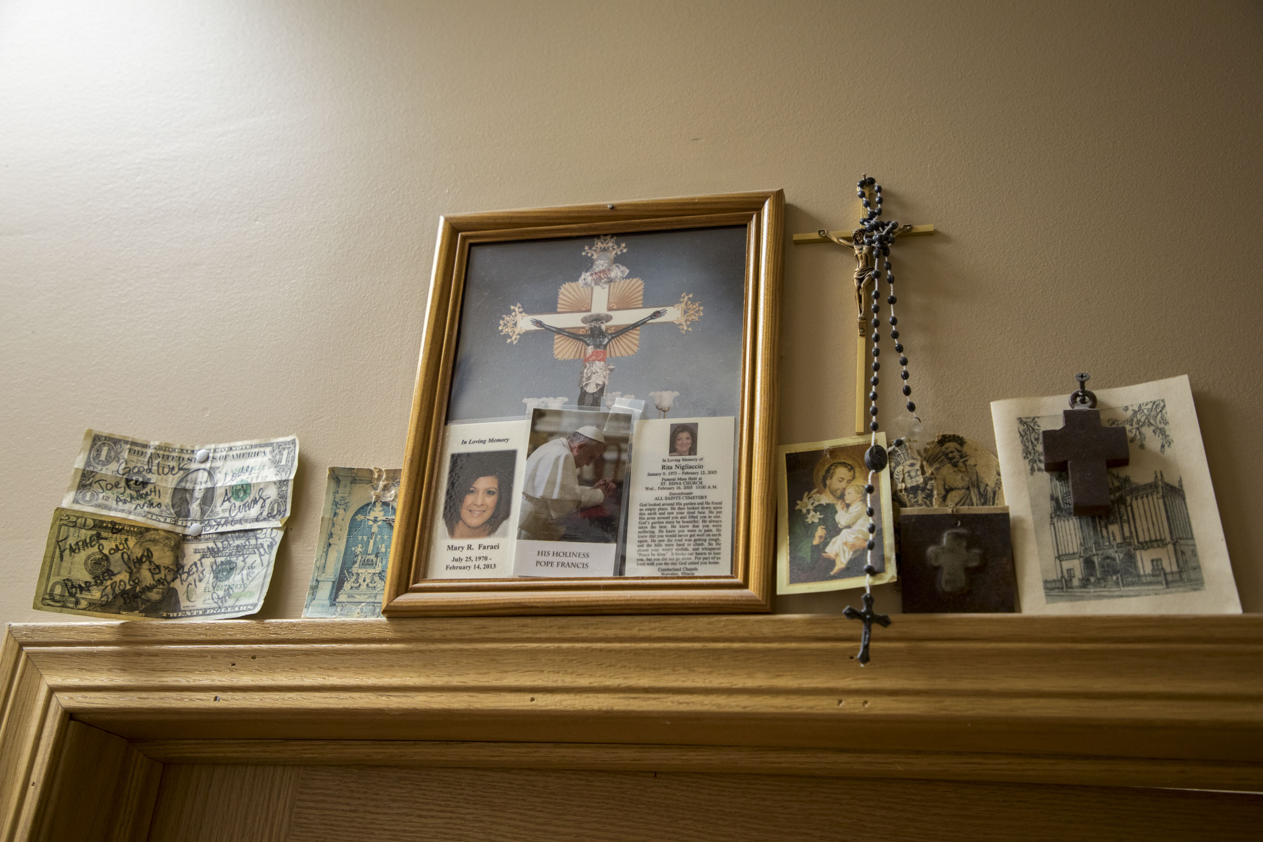 Crucifixes and images of the Virgin Mary hang above a door at Father and Son barbershop. (Andrew Gill/WBEZ)