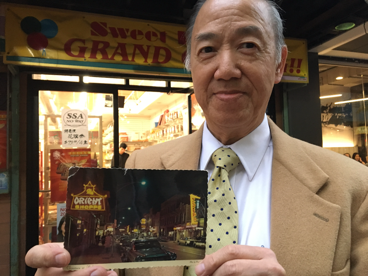 Robert Hoy, who grew up in Chinatown, shows off an old postcard of Wentworth Avenue, Chinatown's original commercial strip. (Odette Yousef/WBEZ)