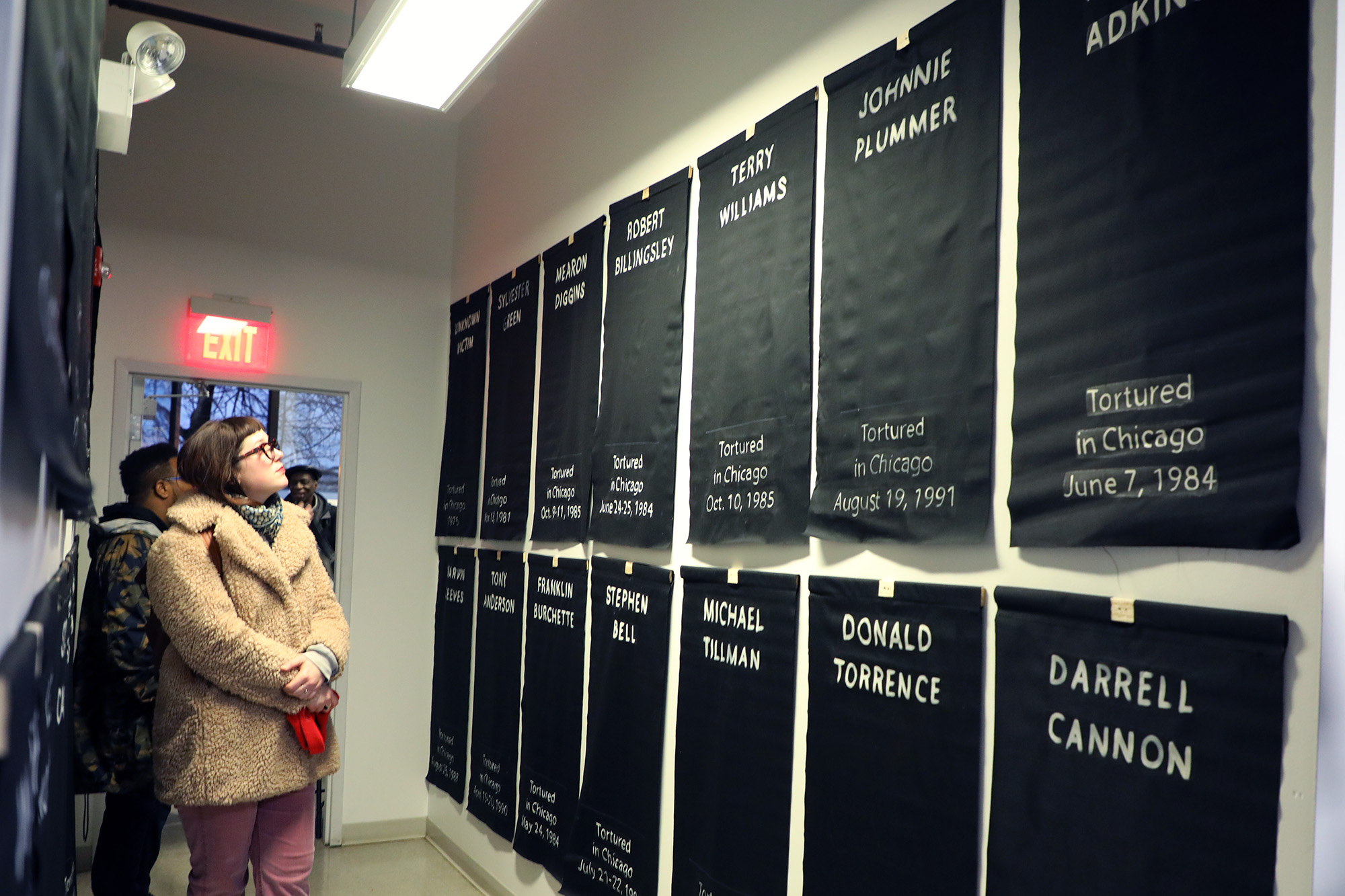 Banners from a 2012 speculative art exhibit that display the names of victims and the dates they were tortured greet visitors as they enter.