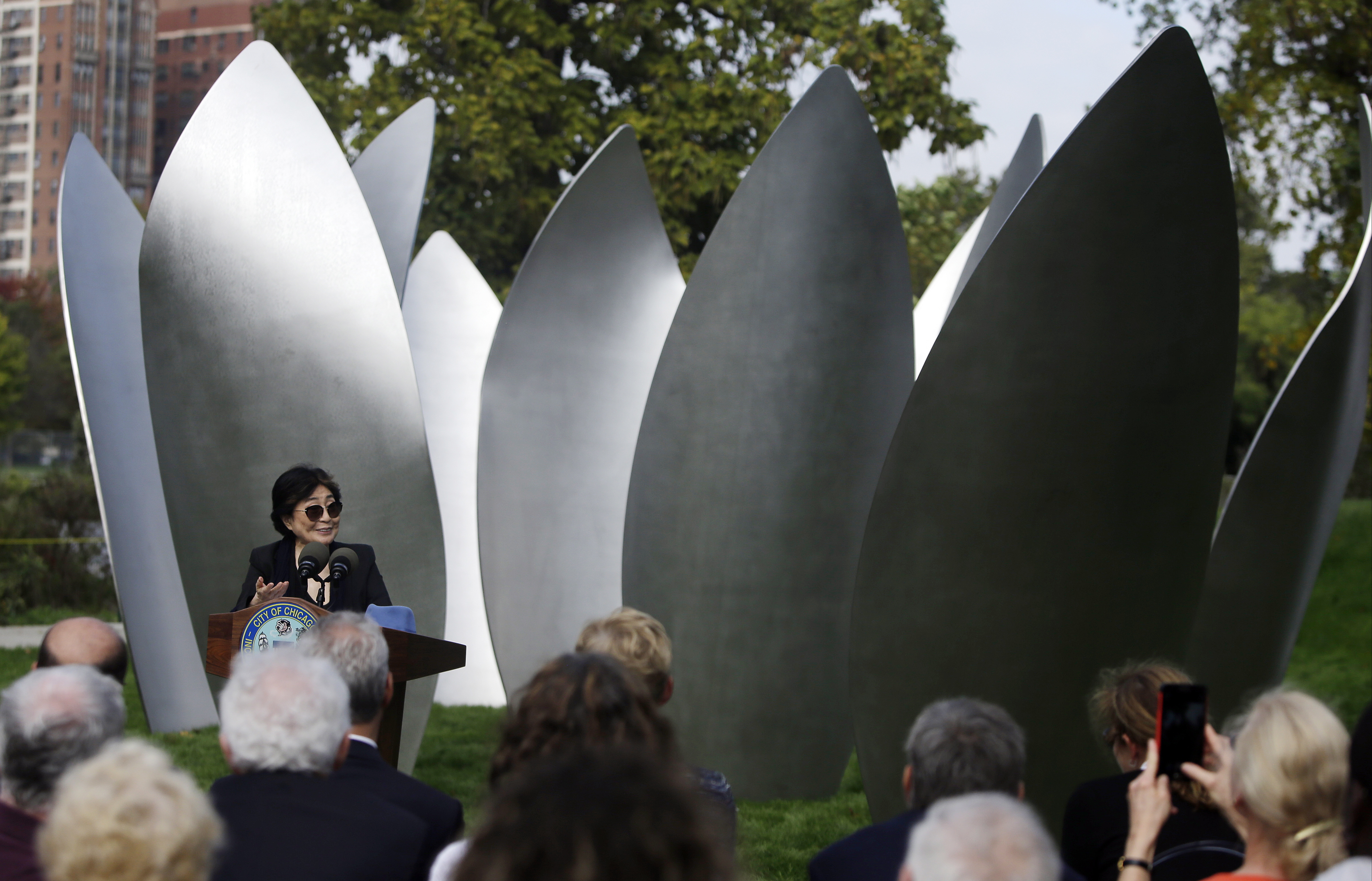 Yoko Ono speaks during the dedication ceremony for her permanent art installation, a sculpture called Sky Landing on Oct. 17, 2016, in Chicago. Sky Landing is Ono's first permanent public art installation in the United States. (AP Photo/Kiichiro Sato).