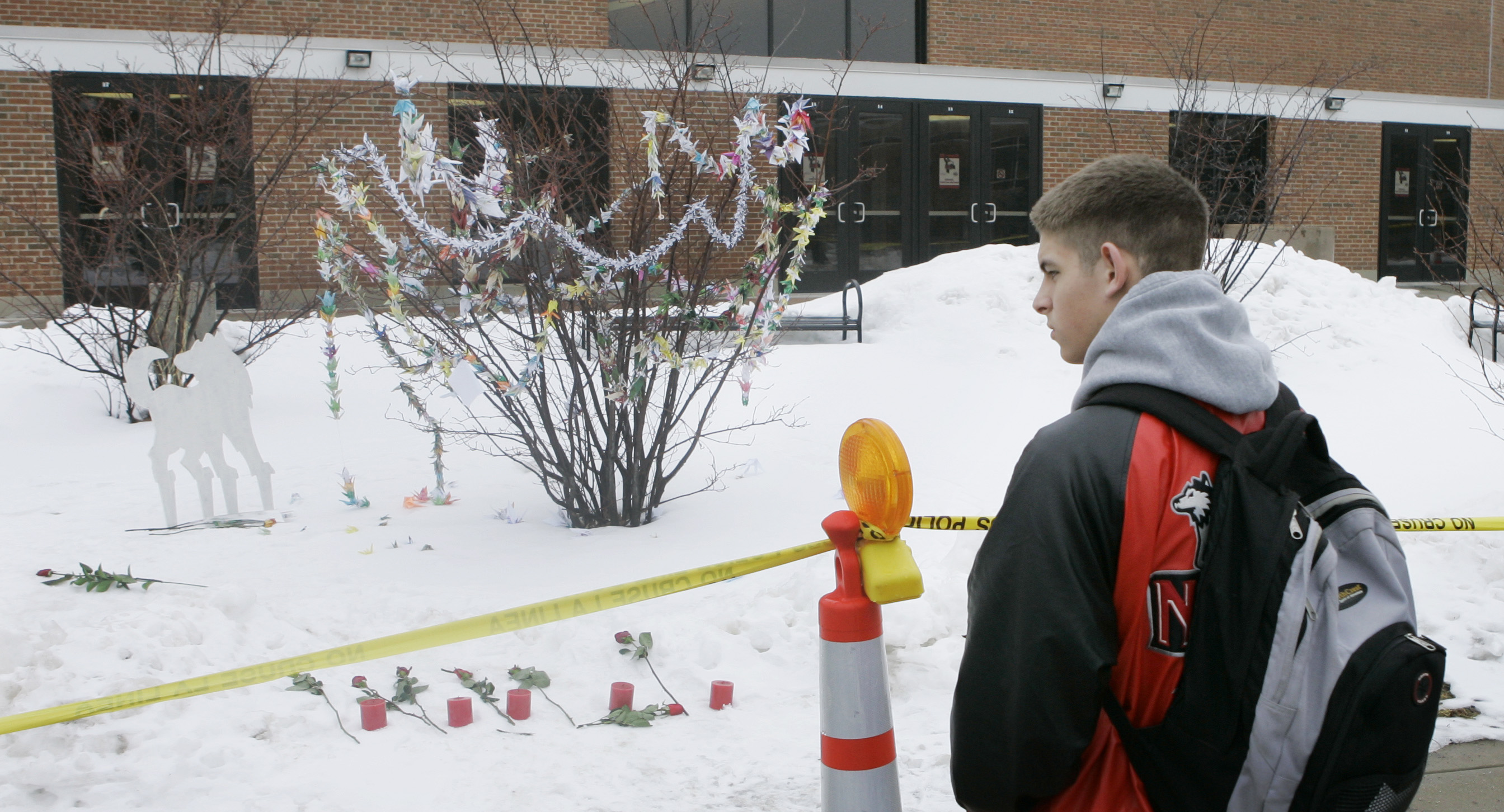 A Northern Illinois University student looks at a small memorial outside Cole Hall on the first day of classes since the Feb. 14, shootings that killed five students in the hall on the Dekalb, Ill., campus Monday, Feb. 25, 2008. (AP Photo/Charles Rex Arbogast)