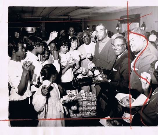 Boxer and heavyweight champion Joe Louis distributes small cartons of milk at a school in 1966. Photo courtesy of the Chicago Defender/Obsidian Collection.