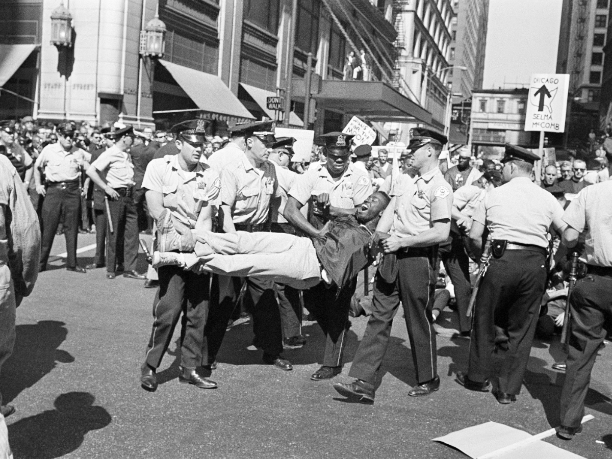 Police carry a demonstrator to a police van after pickets for integration groups broke ranks and sat down at the busy intersection of State and Madison Streets in downtown Chicago, June 15, 1965. Demonstration was the fourth in six days protesting alleged de facto segregation in Chicago's schools.