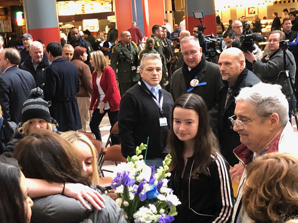 Paul Bauer's 14-year-old daughter, Grace, stands alongside other family members and mourners at a memorial for her father. Bauer, a Chicago police commander, was killed one year ago. (Patrick Smith/WBEZ)