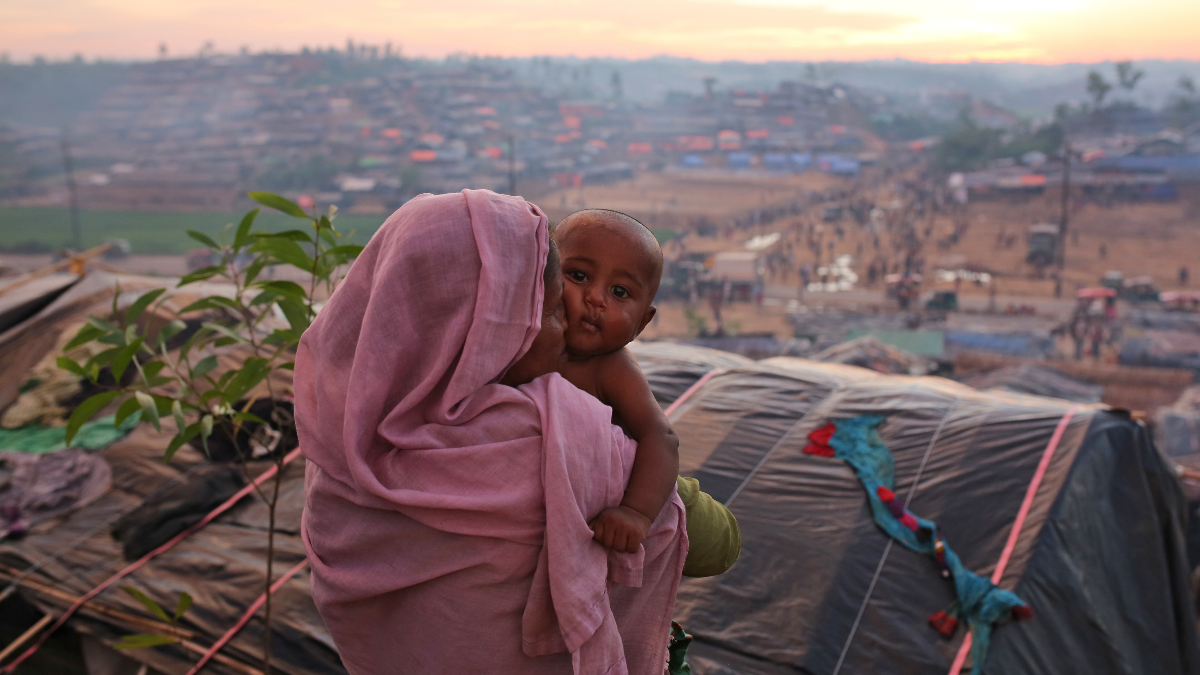 A Rohingya woman carries an infant at Palangkhali refugee camp in Cox's Bazar, Bangladesh, Wednesday, Oct. 4, 2017. More than half a million Rohingya have fled from Myanmar to Bangladesh in just over a month, the largest refugee crisis to hit Asia in decades. (AP Photo/Zakir Hossain Chowdhury).