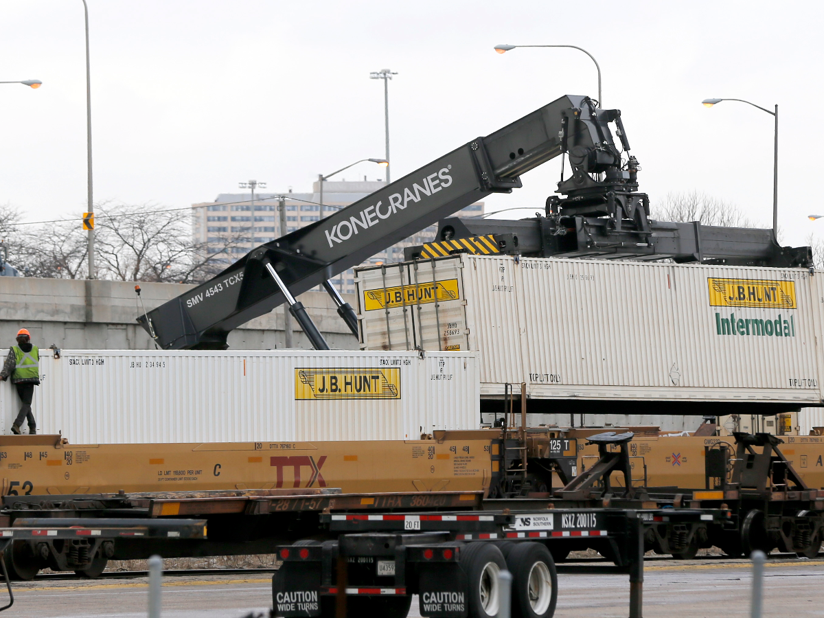 In this Tuesday, Feb. 21, 2017, photo, containers are unloaded from a rail car in the Norfolk Southern rail yard next to Rev. Corey Booker's New Beginnings Church in Chicago. The 2015 heist of over 100 guns, preceded by one in 2014, and another last September from a Chicago rail yard highlight a tragic confluence. Chicago's biggest rail yards are on the gang- and homicide-plagued South and West Sides where most of the city's hundreds of killings happened last year. Residents near the yard are angry the multibillion-dollar railroad isn't doing more to stop the thefts. (AP Photo/Charles Rex Arbogast)