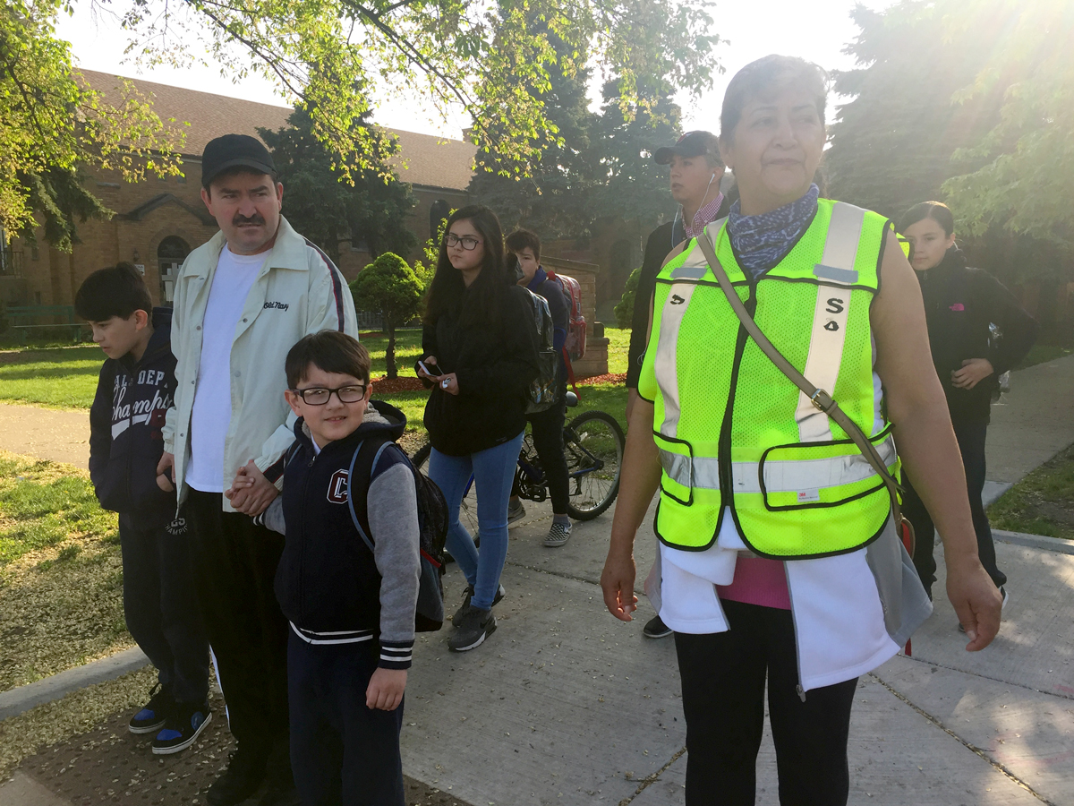 Estela Vasquez helps students and parents cross busy Kedzie Avenue at 46th Street. There used to be a stop sign at the intersection but it was knocked down and never replaced. (Adriana Cardona-Maguigad/WBEZ)
