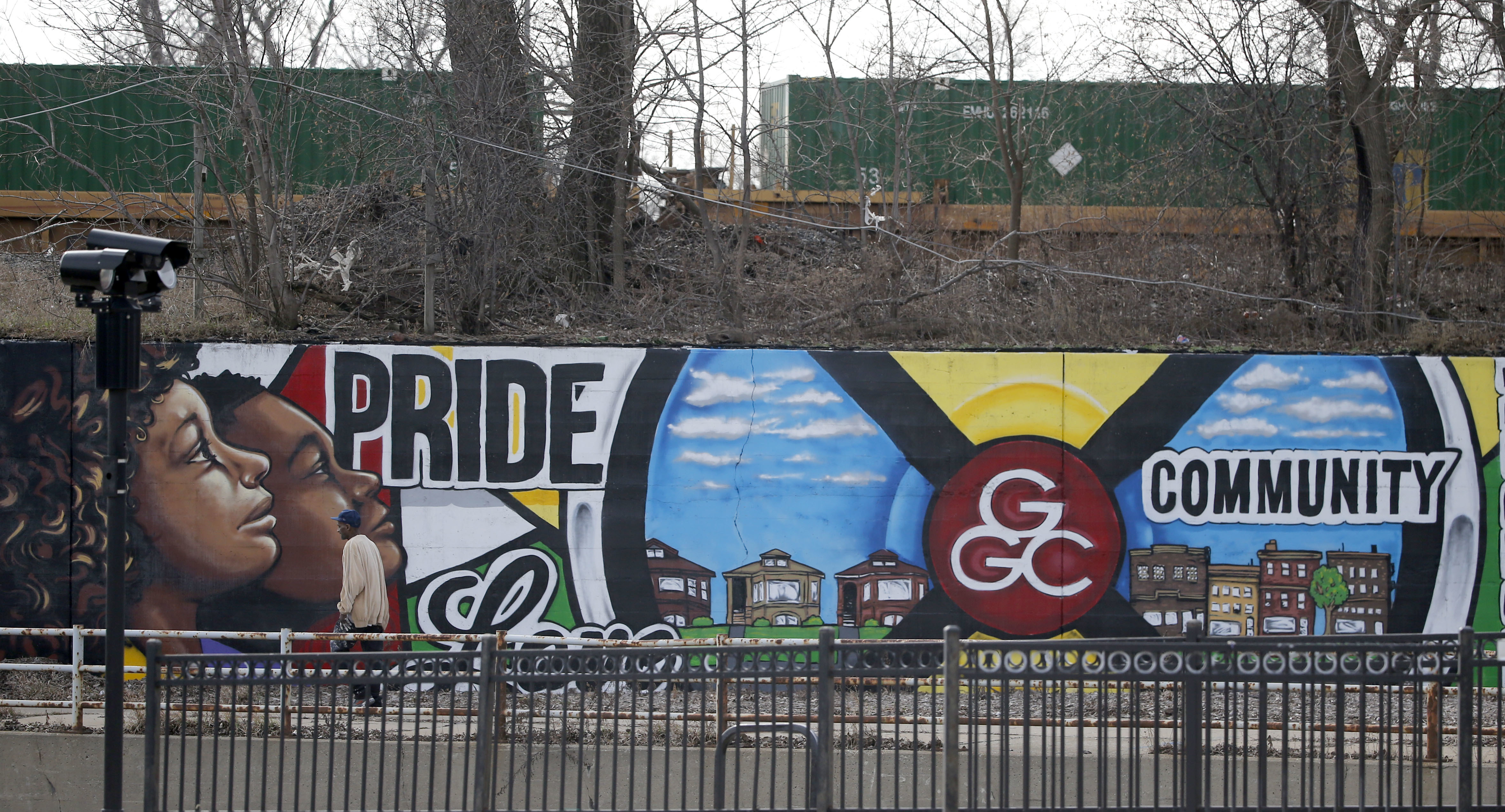 In this Tuesday, Feb. 21, 2017, photo, a lone pedestrian walks past a mural championing the Greater Grand Crossing neighborhood of Chicago where access to the Norfolk Southern rail yard goes unimpeded in Chicago. The 2015 heist of over 100 guns, preceded by one in 2014, and another last September from the same 63rd Street Rail Yard highlight a tragic confluence. Chicago's biggest rail yards are on the gang- and homicide-plagued South and West Sides where most of the city's hundreds of killings happened last year. (AP Photo/Charles Rex Arbogast)