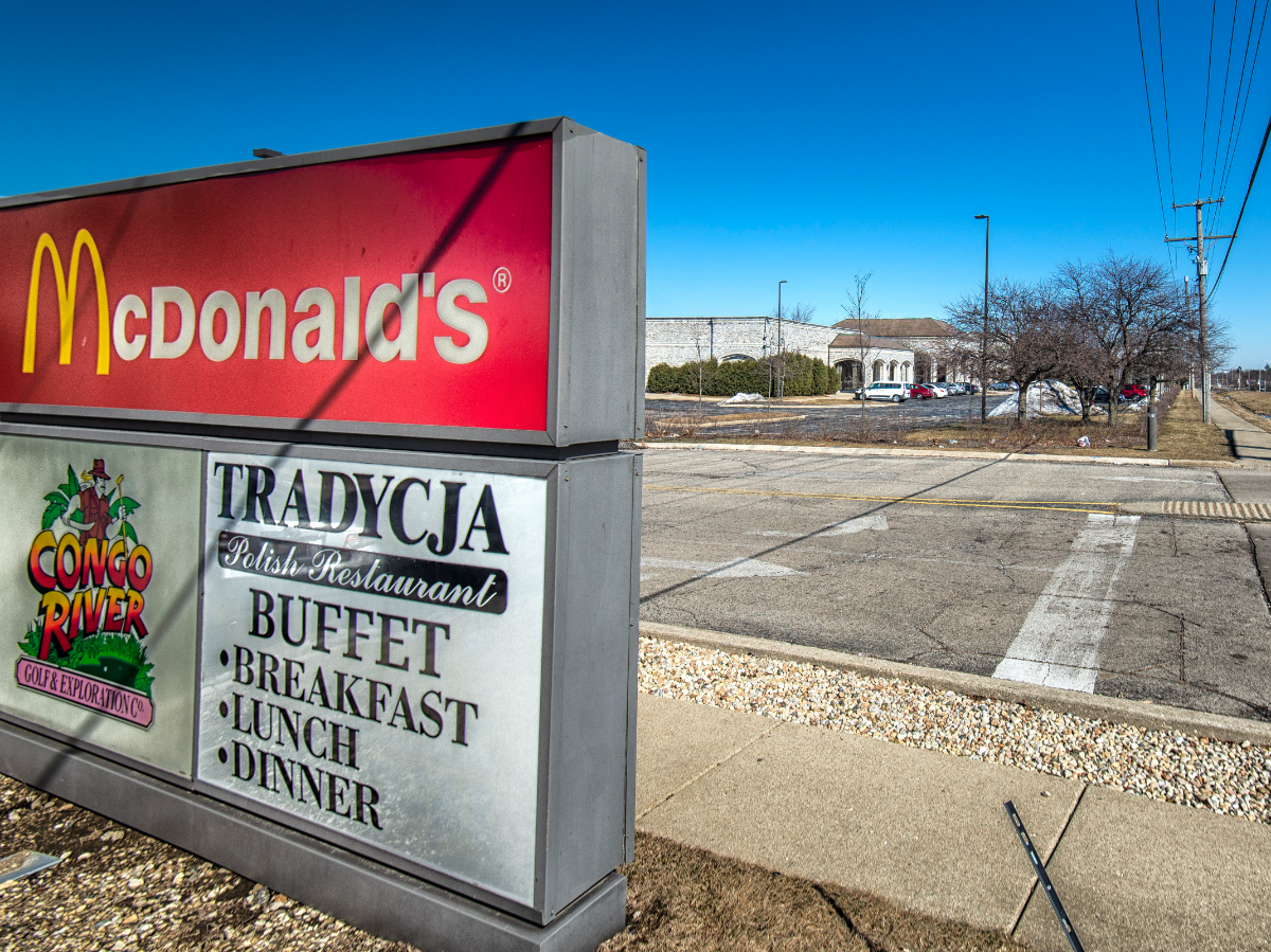 A McDonald's sign in the foreground, with the building housing the presidential papers of Barack Obama in the background