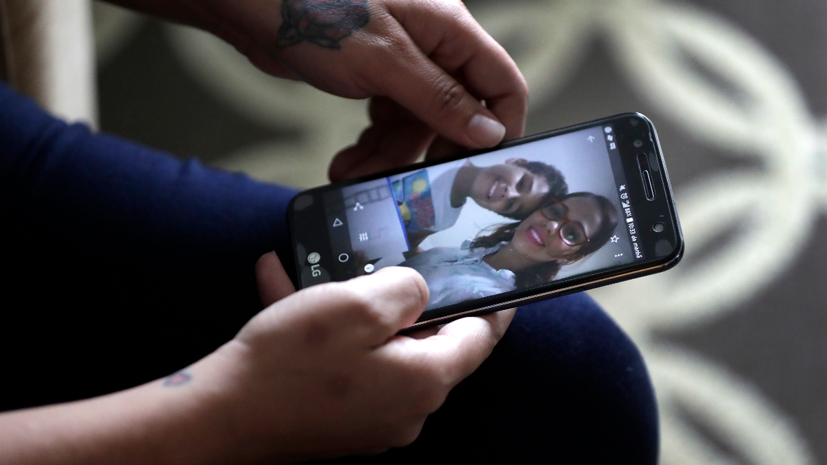 During an interview with The Associated Press Wednesday, June 27, 2018, in Evanston, Illinois, Lidia Karine Souza, who is seeking asylum from Brazil, flips through her phone at photographs of her and her son Diogo as she talks about the ordeal she has lived in searching for and finally seeing her son for the first time on Tuesday. It took Souza weeks to find Diogo after he was taken from her at the Texas border in late May and sent by the government to a Chicago shelter. (Charles Rex Arbogast/AP)