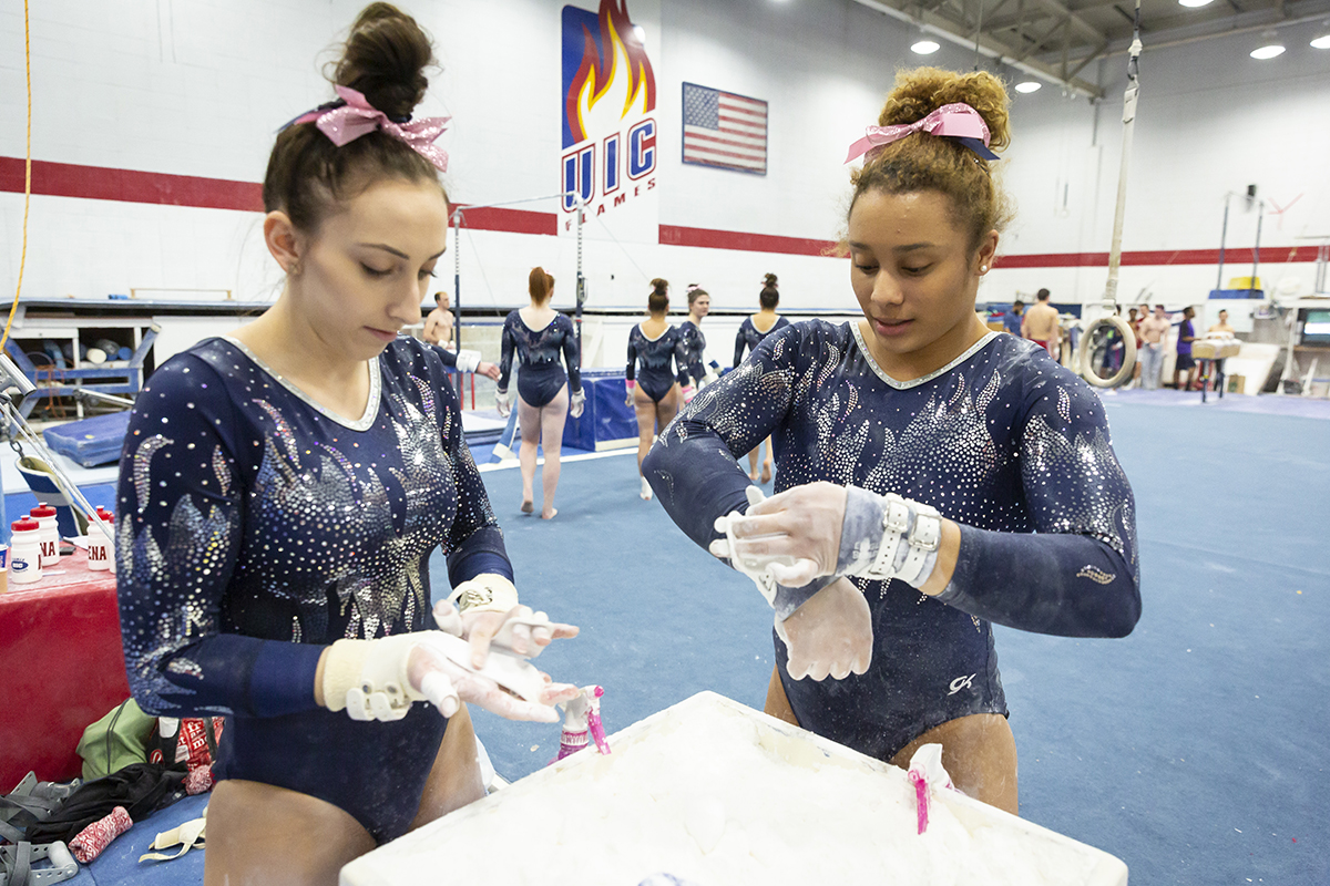 Junior Serena Baker, left, and senior Miki Northern, chalk up before competing on the uneven bars.