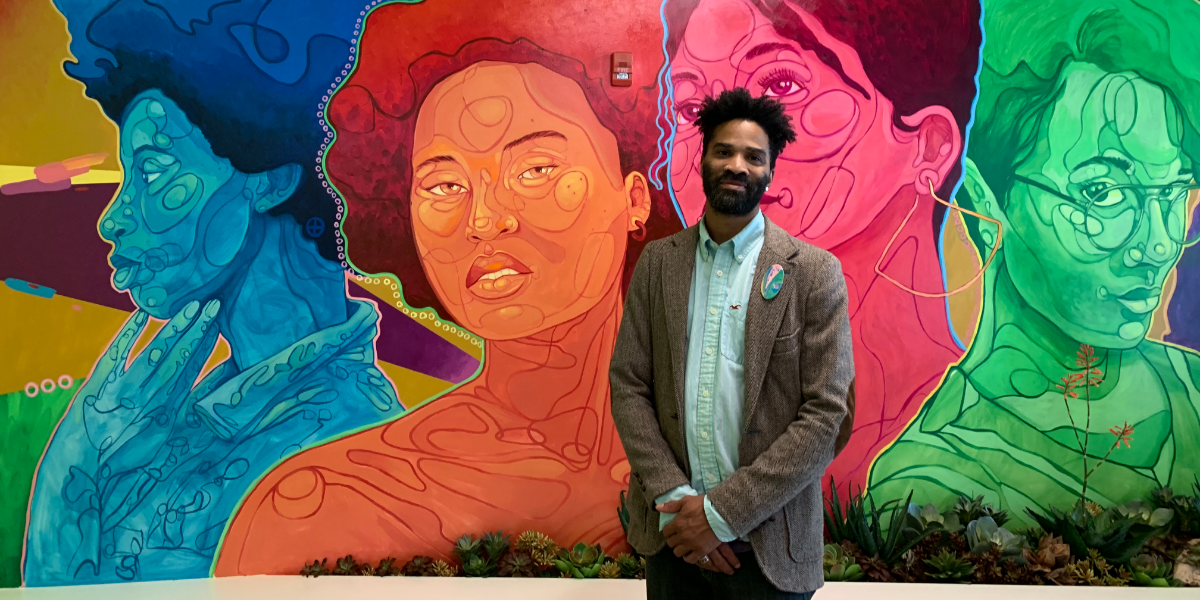 Artist David Anthony Geary in front of his mural of creative Chicago women. The mural is in the front lobby of the building. (WBEZ/Carrie Shepherd)