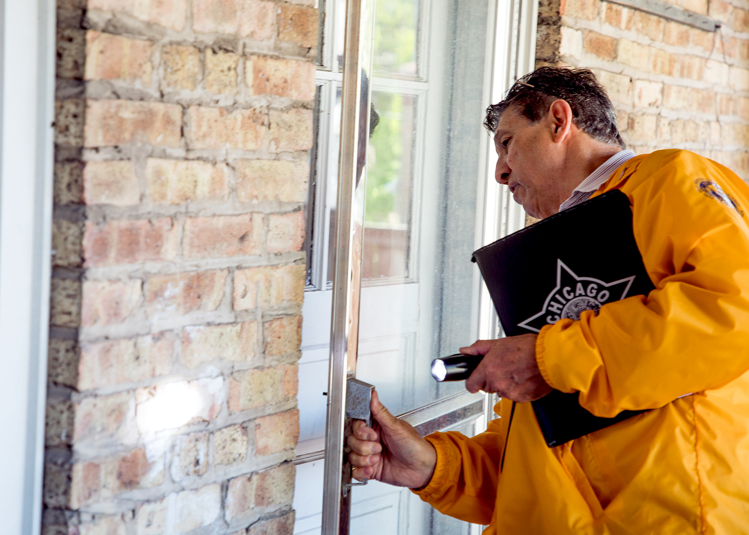 Richard Concaildi checks the back door of a vacant apartment unit in West Rogers Park to make sure it is securely locked. A neighbor had alerted him that it may be occupied by squatters. (Andrew Gill/WBEZ)