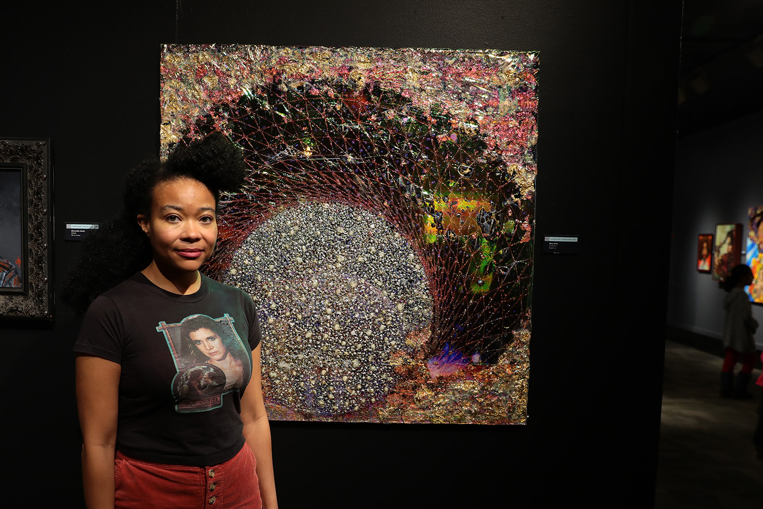 "Artist Rory Scott stands next to one of her pieces, ""ExoGeno II."" (Arionne Nettles/WBEZ)"