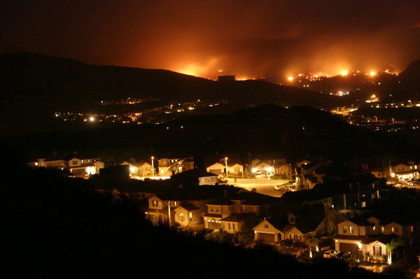 Wildfires burned in the hills of Santa Clarita, Calif., threatening suburban development in October 2007. This fire was among more than a dozen major wildfires, many of which were started from human-related ignitions. (Jeff Turner/Wikimedia)