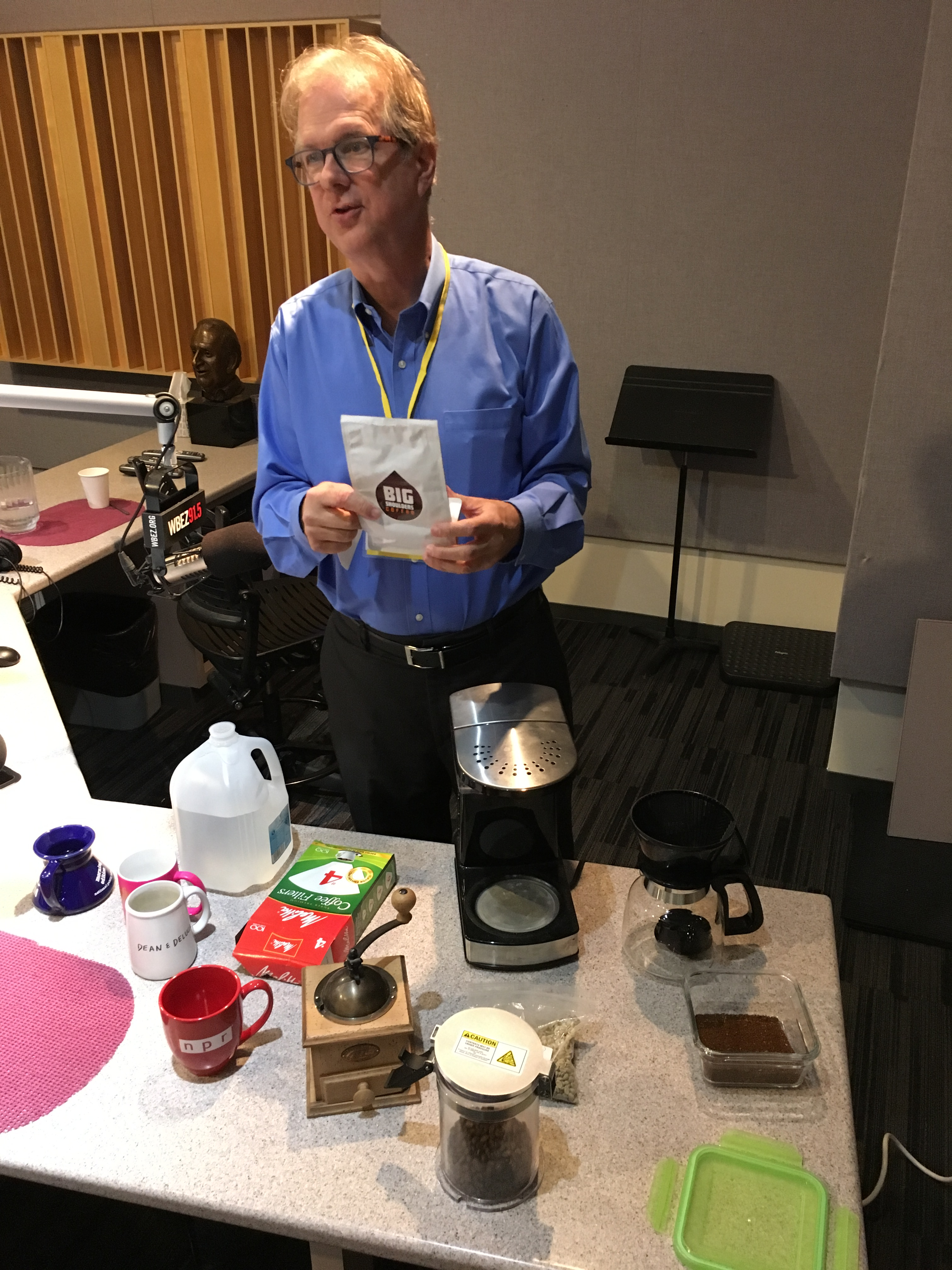Kevin Sinnott, creator of CoffeeCon, showcasing a variety of coffee accouterments in the WBEZ studio.
