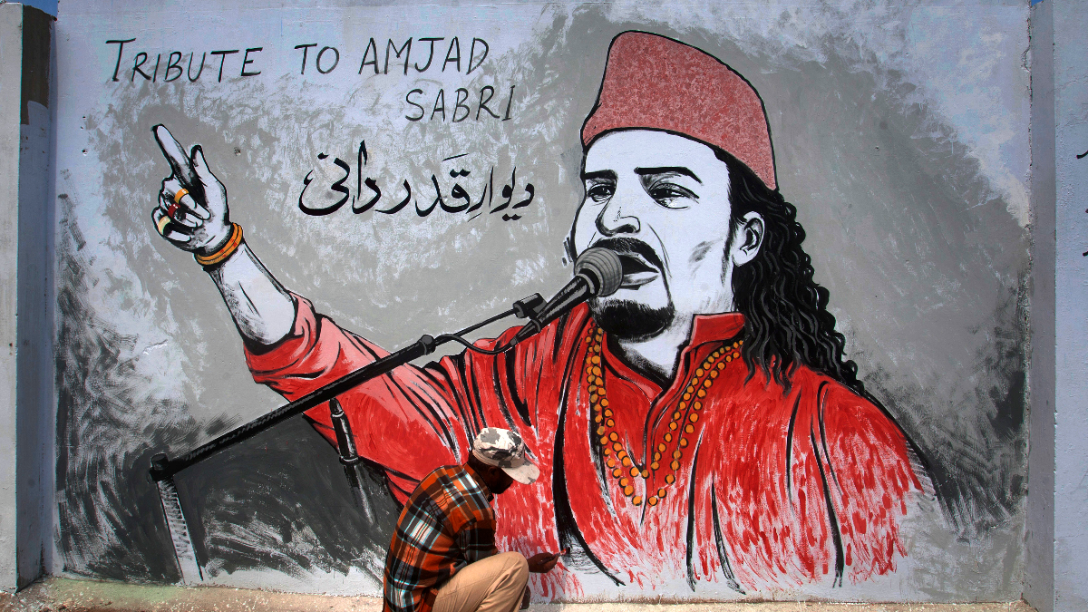 A Pakistani painter puts final touches on a mural of slain Sufi singer Amjad Sabri in Karachi, Pakistan on June 28, 2016. Sabri, a well-known Pakistani Sufi singer, was shot dead in the port city of Karachi in an attack claimed by Islamic extremists. (AP Photo/Shakil Adil).