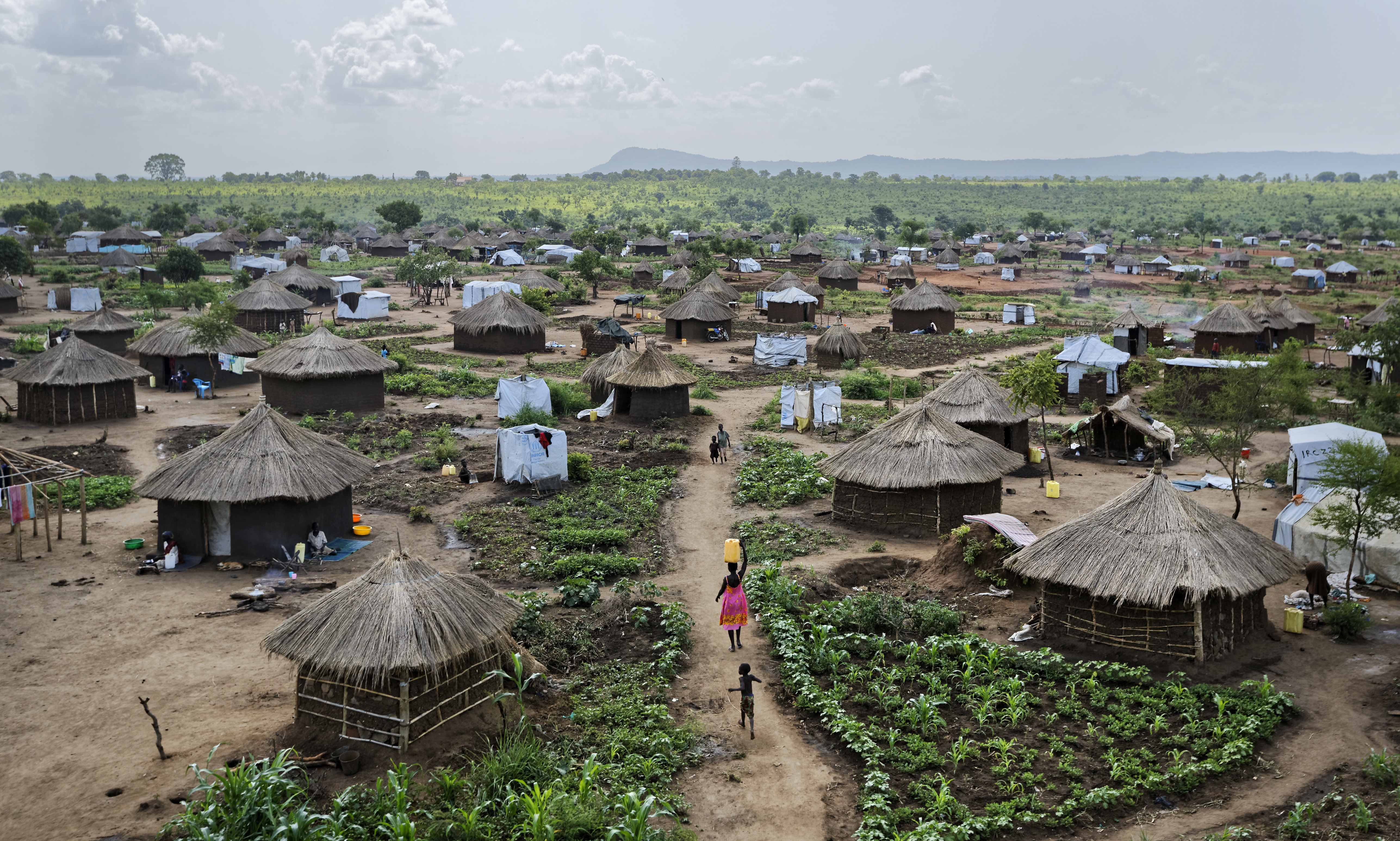 Women and children return to the sprawling complex of mud-brick houses and tents that makes up the Bidi Bidi refugee settlement in northern Uganda on June 9, 2017. The number of South Sudanese refugees sheltering in Uganda has reached 1 million, the United Nations said in August, a grim milestone in what has become the world's fastest-growing refugee crisis. (AP Photo/Ben Curtis)