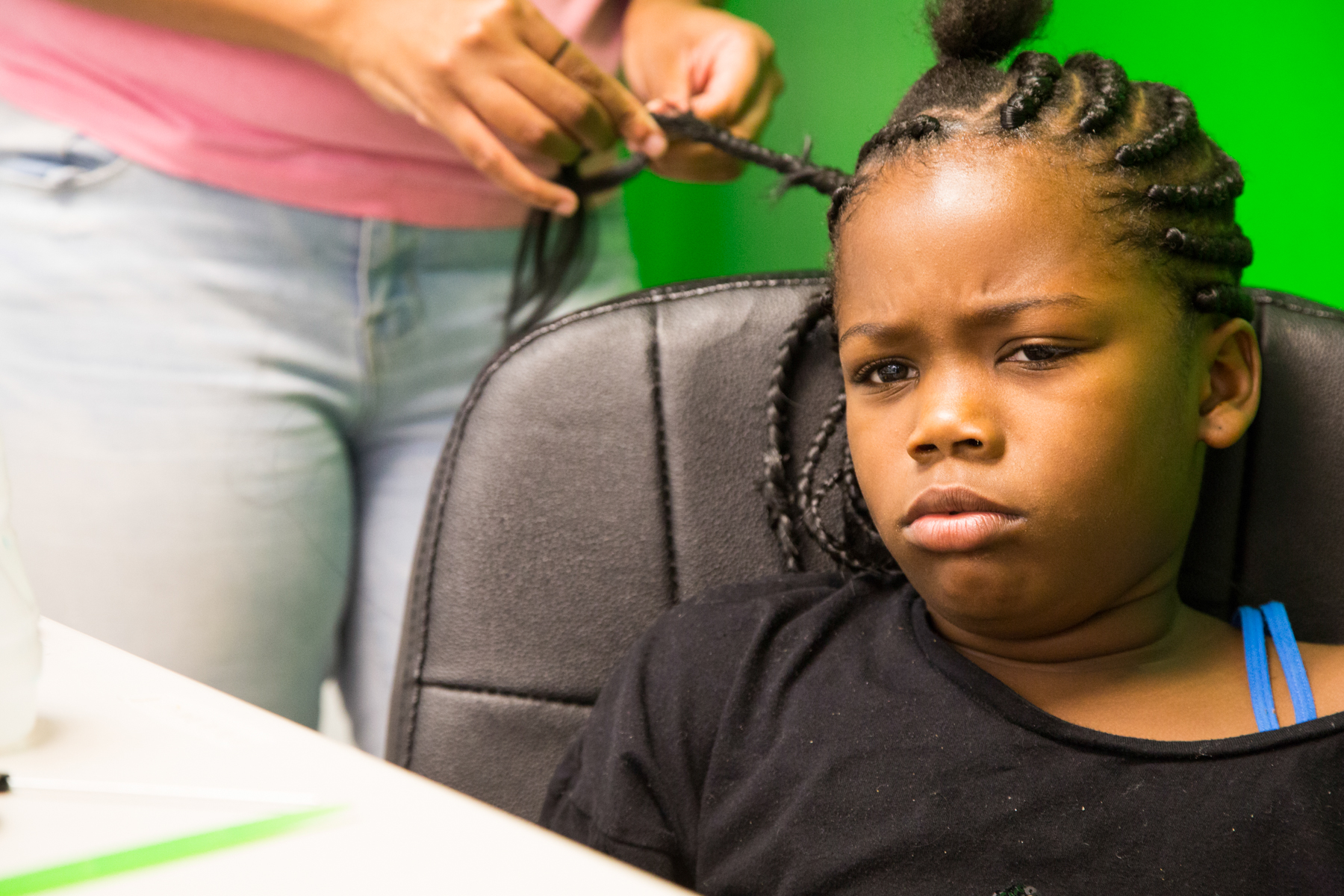 "After more than an hour, Jemiah Frye just wanted to be done. Her stylist, Misha Starks, remembers getting her own hair braided as a young child. ""It just took too long, I just wanted to get up. Once they sit here for a while, they get all fidgety,"" said Starks. Jemiah braids the hair on her dolls and toy ponies. (John Fecile/WBEZ)"