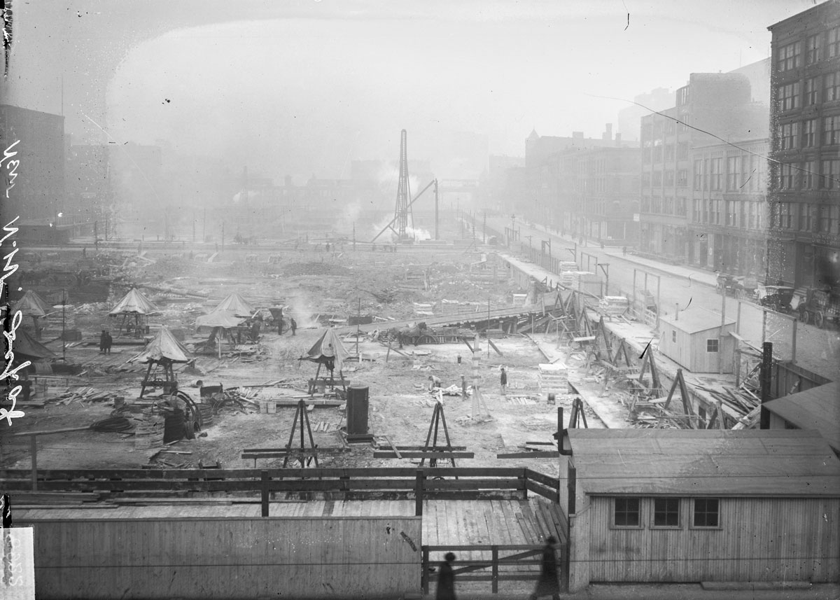 View of the laying of foundations for the new Chicago & Northwestern Railway Station at 500 West Madison Street in the Near West Side community area of Chicago, Illinois. The station filled the area between North Canal, North Clinton, West Madison and West Lake Streets. In this image, a small building is visible in the foreground.