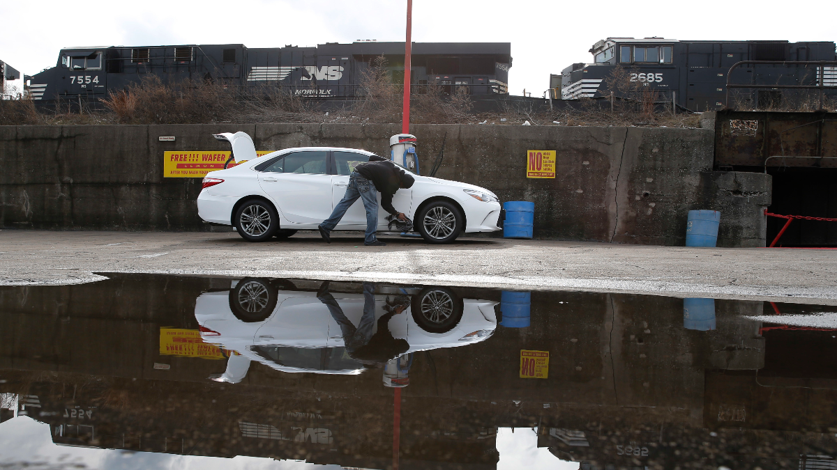In this Tuesday, Feb. 21, 2017, photo, a patron of a Grand Crossing neighborhood car wash finishes off cleaning his car next to several Norfolk Southern train locomotives in Chicago. The 2015 heist of over 100 guns, preceded by one in 2014, and another last September from a Chicago rail yard highlight a tragic confluence. Chicago's biggest rail yards are on the gang- and homicide-plagued South and West Sides where most of the city's hundreds of killings happened last year. Residents near the yard are angry the multibillion-dollar railroad isn't doing more to stop the thefts. (AP Photo/Charles Rex Arbogast)