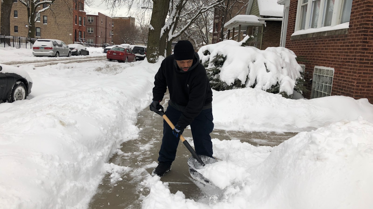 Michael Williams, a lifelong Englewood resident, shovels out the sidewalks near his home. (Greta Johnsen/WBEZ)