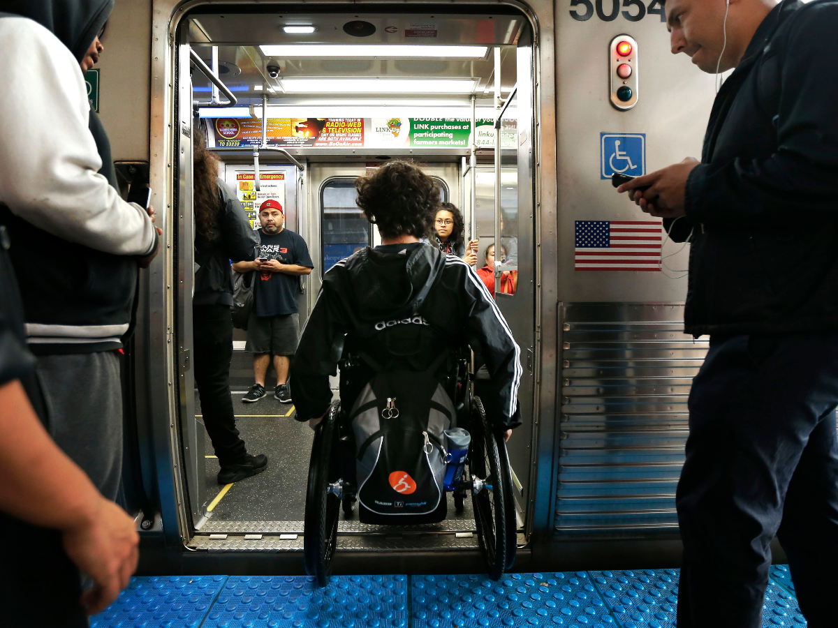 Jonathan Annicks maneuvers his wheelchair onto a pink-line train after a day at DePaul University in Chicago in September 2016. He was paralyzed by a gunshot wound from an unidentified assailant in April. (AP Photo/Charles Rex Arbogast)