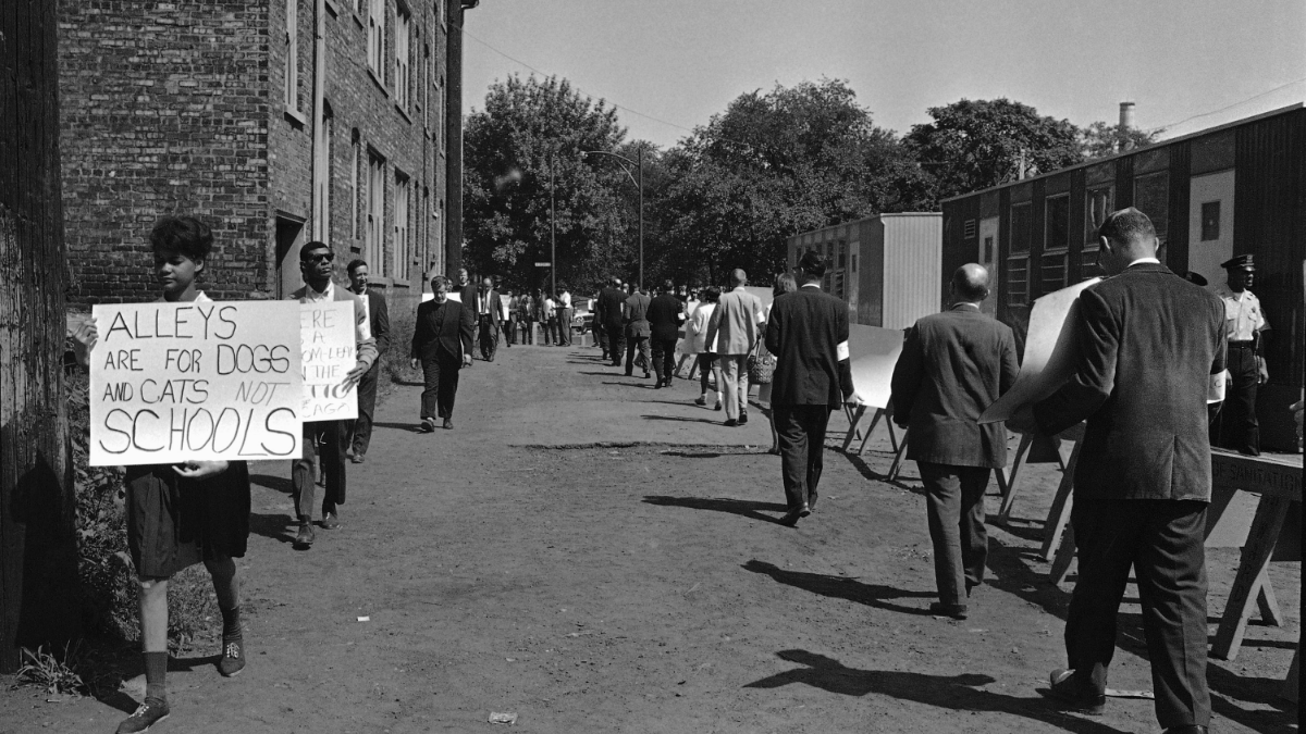 Clergymen march in an alley on the South Side of Chicago on Aug. 15, 1963, where workmen are installing mobile classrooms. African American organizations, contending such temporary facilities maintain segregation, argue that African American students who would use them should be sent, instead, to uncrowded white schools.