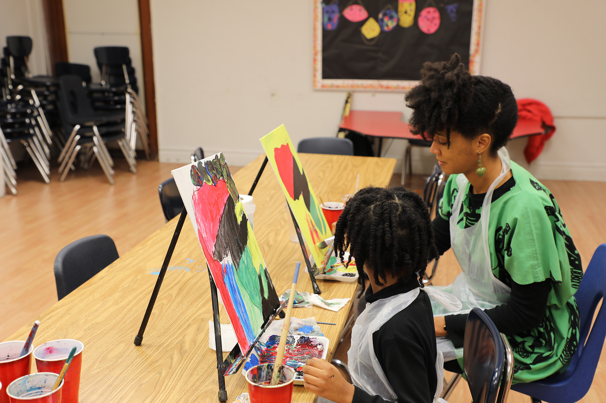 Lecretia Akines and her daughter paint during the Super Karamu event. (Arionne Nettles/WBEZ)